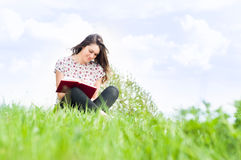 Summer relaxation concept with beautiful girl sitting on meadow. And writing in her journal with copy space or advertising area Stock Images