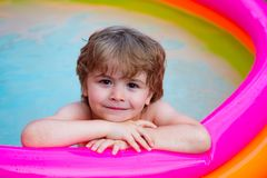 Summer relaxation in the pool. A child lies and relax in a home pool with a smile. Summer rest. Vacations. Cute baby royalty free stock image
