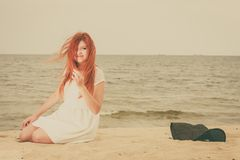 Redhead adult woman lying on beach Stock Image