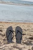Summer flip flops in the sand. Summer relaxations. Flip flops in the sand on the beach. Holiday feeling stock photography