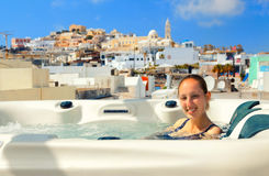 Summer resort in Fira, Santorini. Young woman enjoying outside jacuzzi. In background - the center of Fira, Santorini Royalty Free Stock Images