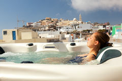 Summer resort in Fira, Santorini. Young woman enjoying outside jacuzzi. In background - the center of Fira, Santorini Stock Images