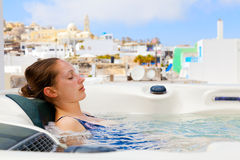 Summer resort in Fira, Santorini. Young woman enjoying outside jacuzzi. In background - the center of Fira, Santorini Royalty Free Stock Photo