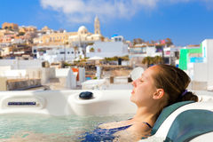 Summer resort in Fira, Santorini. Young woman enjoying outside jacuzzi. In background - the center of Fira, Santorini Royalty Free Stock Photography