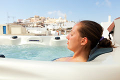Summer resort in Fira, Santorini. Young woman enjoying outside jacuzzi. In background - the center of Fira, Santorini Stock Photo