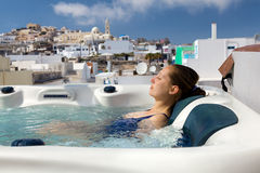 Summer resort in Fira, Santorini. Young woman enjoying outside jacuzzi. In background - the center of Fira, Santorini royalty free stock image