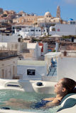 Summer resort in Fira, Santorini. Young woman enjoying outside jacuzzi. In background - the center of Fira, Santorini. Vertical shot Royalty Free Stock Photos
