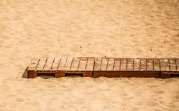 Summer resort. Wooden sidewalk on a sandy beach. Royalty Free Stock Photo