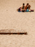 Summer resort. Wooden sidewalk on a sandy beach. Stock Images