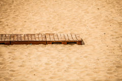 Summer resort. Wooden sidewalk on a sandy beach. Royalty Free Stock Images