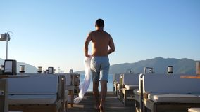 Summer resort, young man undresses on move and jumps from pier to blue sea at expensive holiday. Summer resort, young man undresses on move and jumps from pier stock video