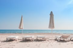 Summer rest on sea beach background. Deckchair or sunbeds with umbrellas on white sand of resort beach on sunny clear day Stock Photo