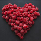 Summer ripe raspberry in the shape of hart. On dark black background Royalty Free Stock Images