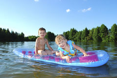 Summer on the river boy and girl floating on an air mattress. Royalty Free Stock Image