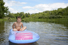 Summer on the river boy sits on an inflatable mattress on the ri Stock Photos