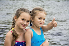 In the summer on the river, two small sisters in bathing suits a stock photo
