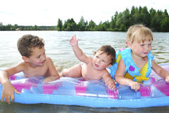 Summer on the riverchildren floating on an air mattress. Royalty Free Stock Image