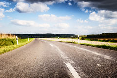 Summer road with cloudy sky Stock Image