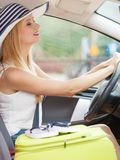 Pretty woman sit in car with suitcase royalty free stock photography