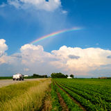 Summer Road Trip. Truck driving through a scenic summer midwest landscape with soybean field and rainbow above