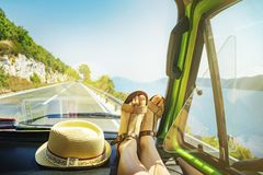 Summer road trip with young female legs on dashboard inside of classic oldtimer van cruising alongside sea coast stock photo