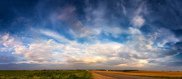 Summer road under awesome clouds on the sky panorama. Summer travel through the fields after storm royalty free stock image