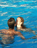 Summer romance. A young couple in the pool royalty free stock image