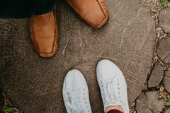 Summer romance. Legs of  man and woman on  wooden walkway. Summer romantic date. The legs of a woman and a man stand on a path made from cropped round arches royalty free stock photos