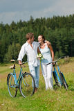 Summer - Romantic couple with bike in meadow Royalty Free Stock Photography