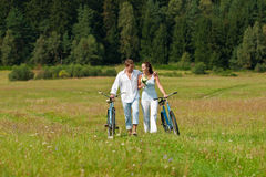 Summer - Romantic couple with bike in meadow Stock Images