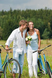 Summer - Romantic couple with bike in meadow Stock Photo