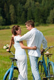 Summer - Romantic couple with bike in meadow Royalty Free Stock Photos
