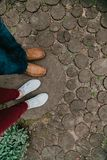Summer romance. Legs of  man and woman on  wooden walkway. Summer romantic date. The legs of a woman and a man stand on a path made from cropped round arches royalty free stock photography