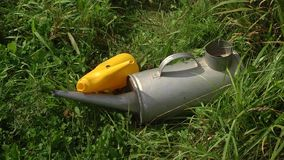 Summer rural landscape with a blossoming meadow.A small yellow plastic watering can and a large metal watering can lie on the gras stock footage