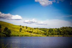 Summer rural landscape with the lake, rolling hills, trees and b Stock Photos