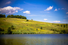 Summer rural landscape with the lake, rolling hills, trees and b Royalty Free Stock Images
