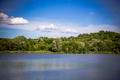 Summer rural landscape with the lake, rolling hills, trees and b Royalty Free Stock Photography