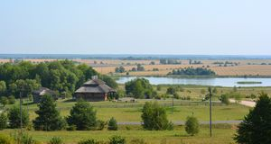 Summer rural landscape with old cottage and lake in Belarus royalty free stock image