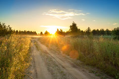 Summer rural landscape with sunrise , fog and the road Royalty Free Stock Images