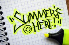`SUMMER`S HERE` graffiti tag in notebook. In yellow and black with bright yellow highlighter.  Landscape format Stock Photography