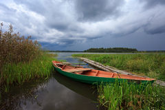 Summer's Russian lake scenery with wooden boat Stock Images