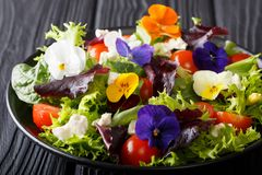 Summer salad of edible flowers with lettuce, spinach, tomatoes a. Nd feta close-up on the table. horizontal royalty free stock photos