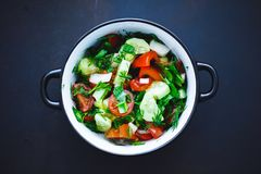 Summer salad of fresh vegetables in a plate on a black background, tomatoes, cucumbers, dill, parsley, onion. Close up. royalty free stock photo