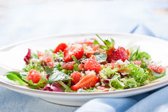 Summer salad with grapefruit, strawberry, mint, balsamic and cheese on a plate on a wooden background Stock Photo
