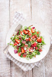 Summer salad with grapefruit, strawberry, mint, balsamic and cheese on a plate on a wooden background Stock Image