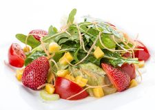 Summer salad with strawberries and tomatoes. On a white plate. On white background royalty free stock images