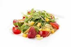 Summer salad with strawberries and tomatoes. On a white plate stock photos