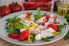 Summer salad with turkey breast, greens, tomato and mozzarella. Wooden background. Top view. Close-up Stock Photos