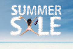 Summer sale clouds with excited woman jumping Royalty Free Stock Photo
