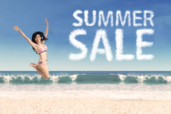 Summer sale clouds and jumping woman 1. Summer sale clouds and woman jumping at beach Royalty Free Stock Image